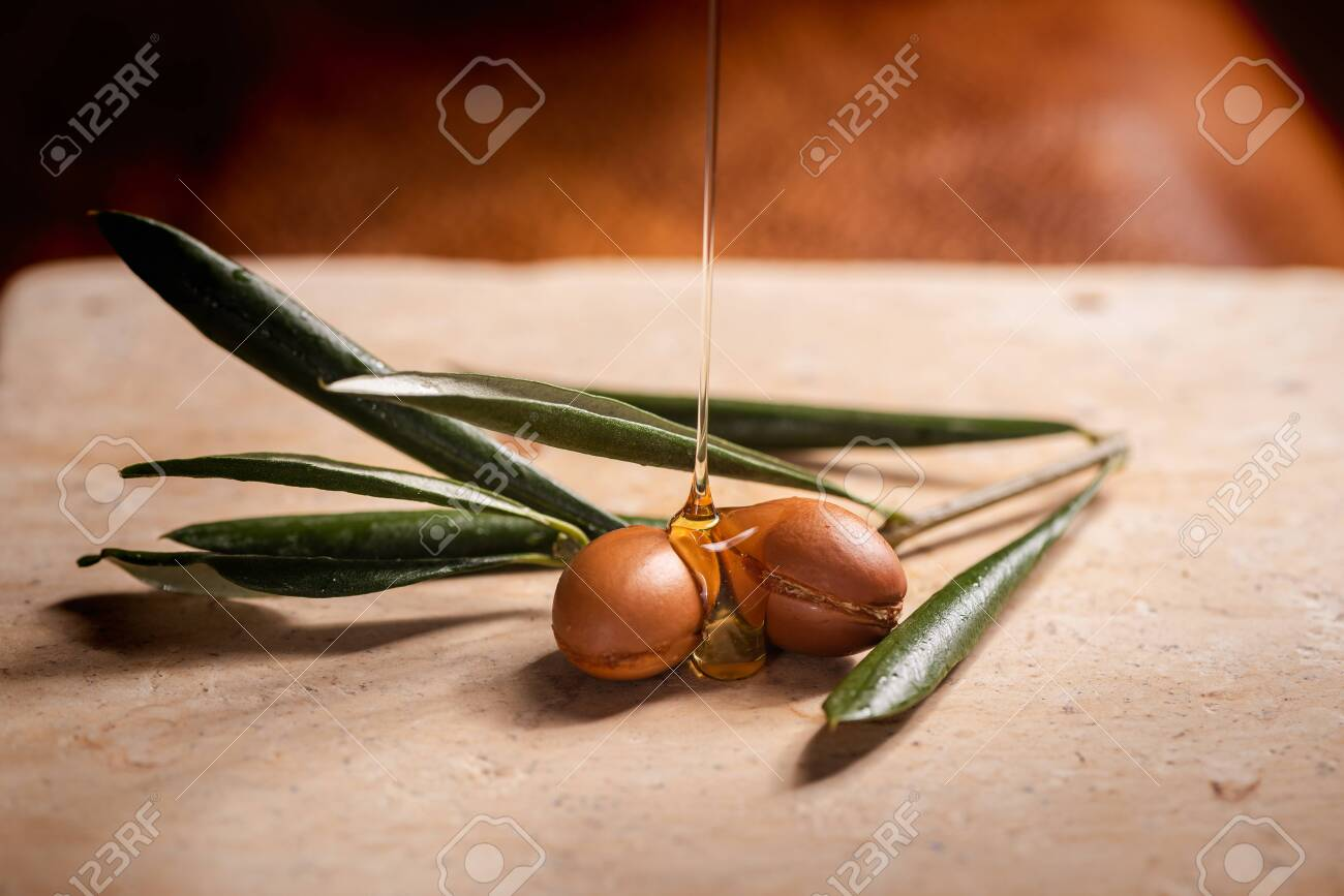 Argan oil, used for cosmetics, puring over two argan seeds on a stone table. - 133231434
