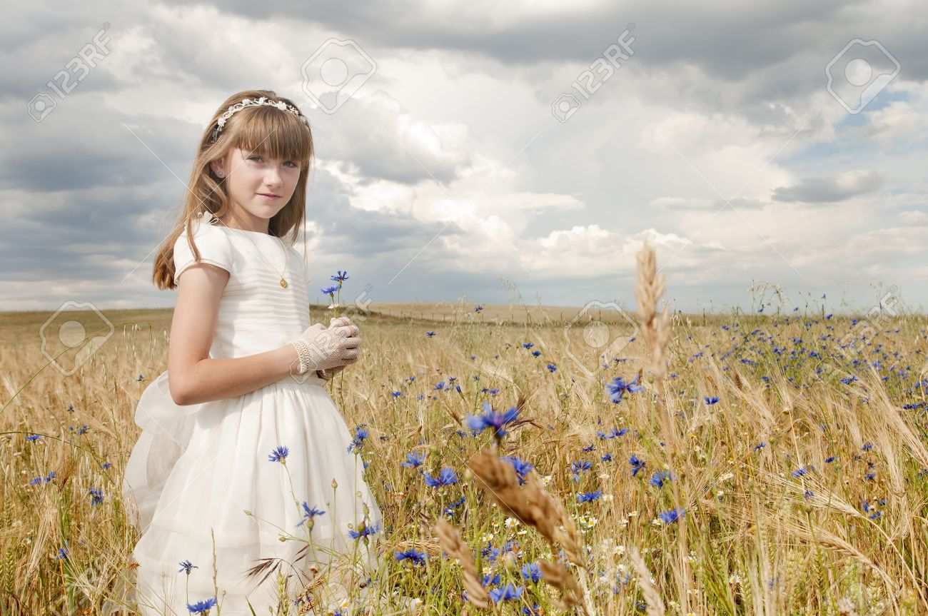 girl wearing first communion dress among the flowers and spikes Stock Photo - 10263569