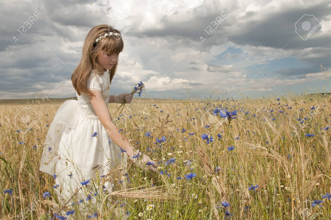 girl wearing first communion dress among the flowers and spikes Stock Photo - 10082260