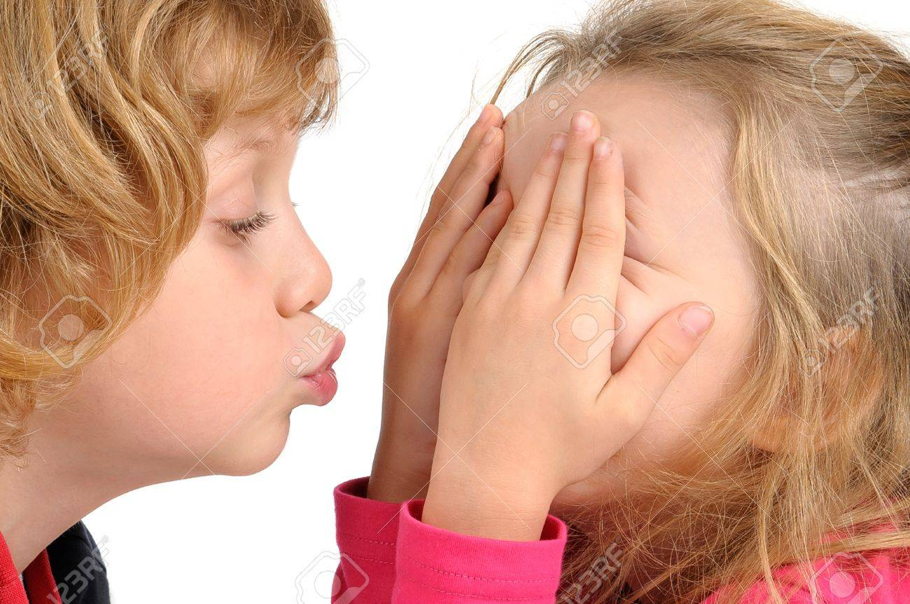Young Boy Trying To Kiss A Girl Isolated In White Stock Photo