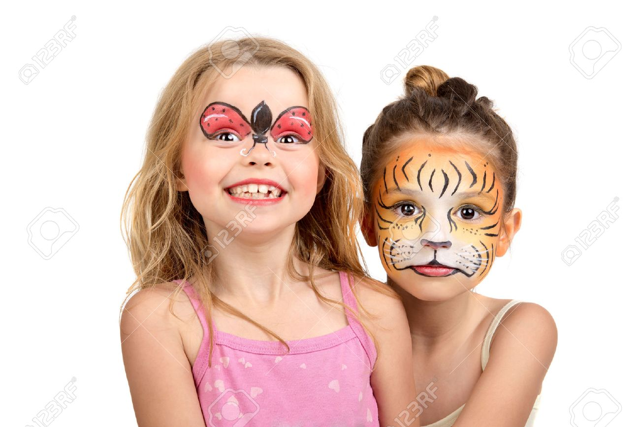 youngster girls face painting: Beautiful young girls with painted faces, tiger and ladybug