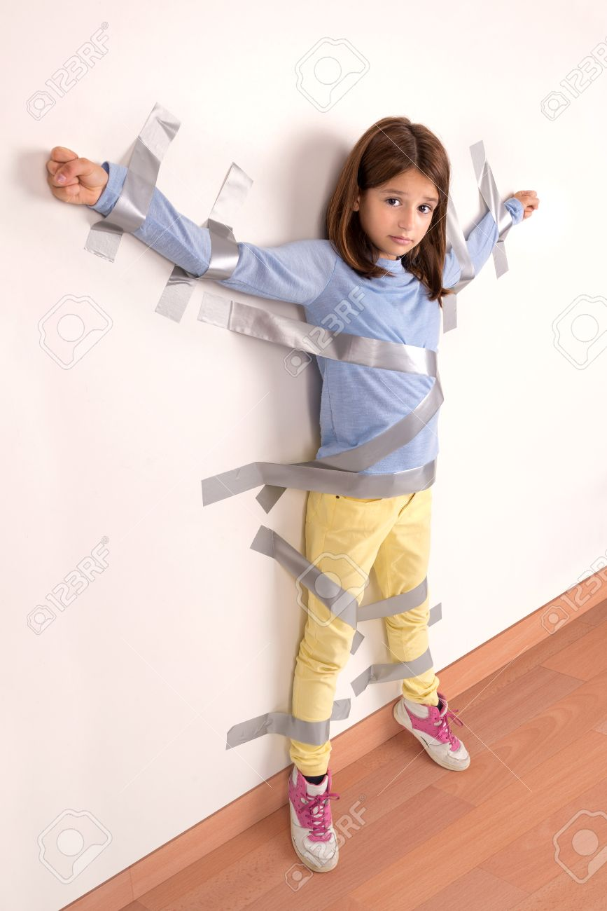 littlegirl tied up Stock Photo - Young girl tied to the wall with duct tape