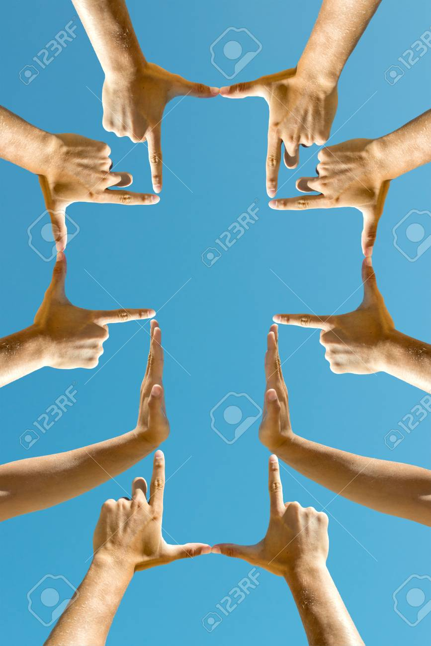 Hands forming a cross against the blue sky - 88974465