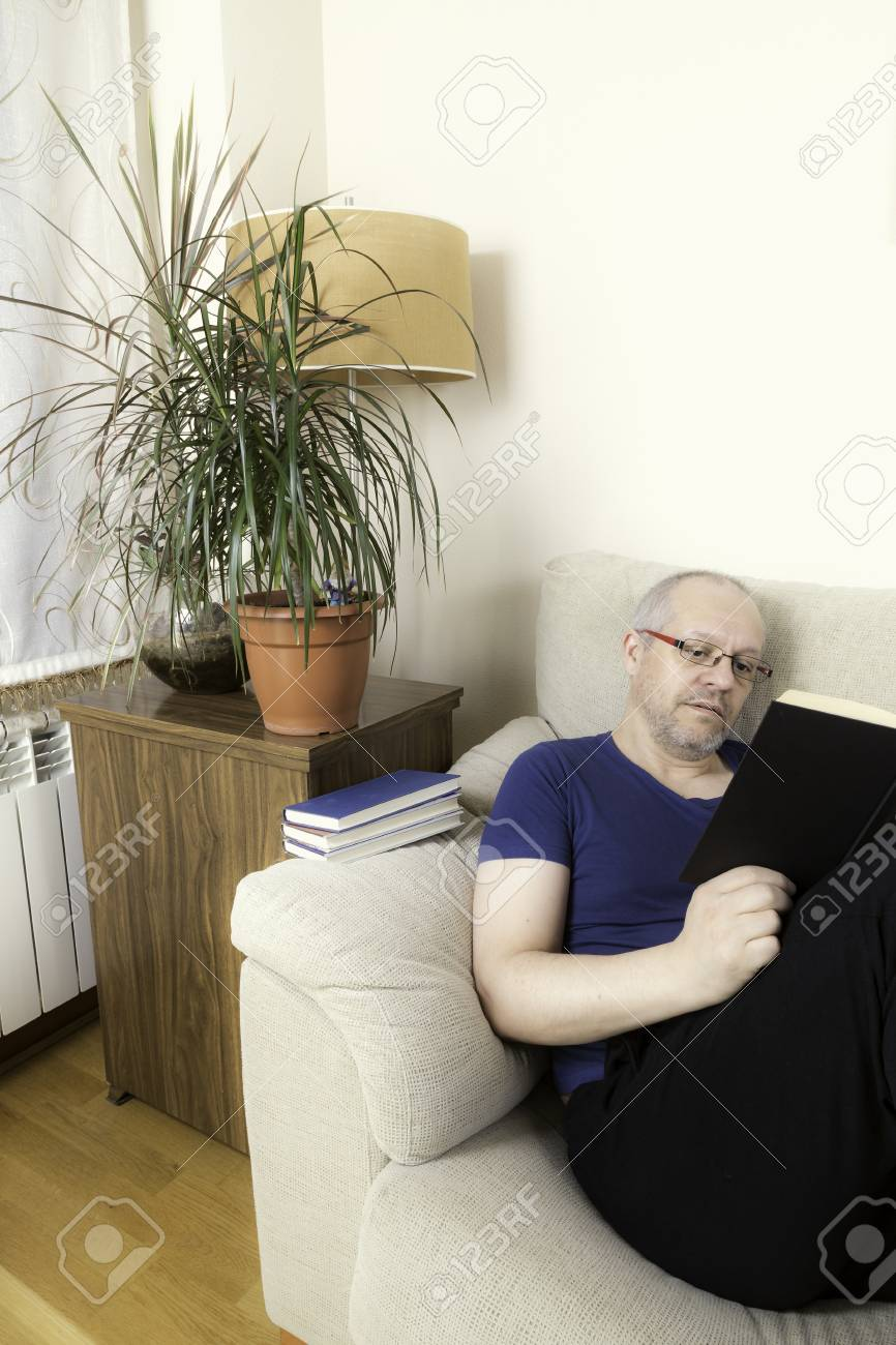 Man With Glasses Reading A Book On A Sofa Next To Some Green Plants Stock  Photo