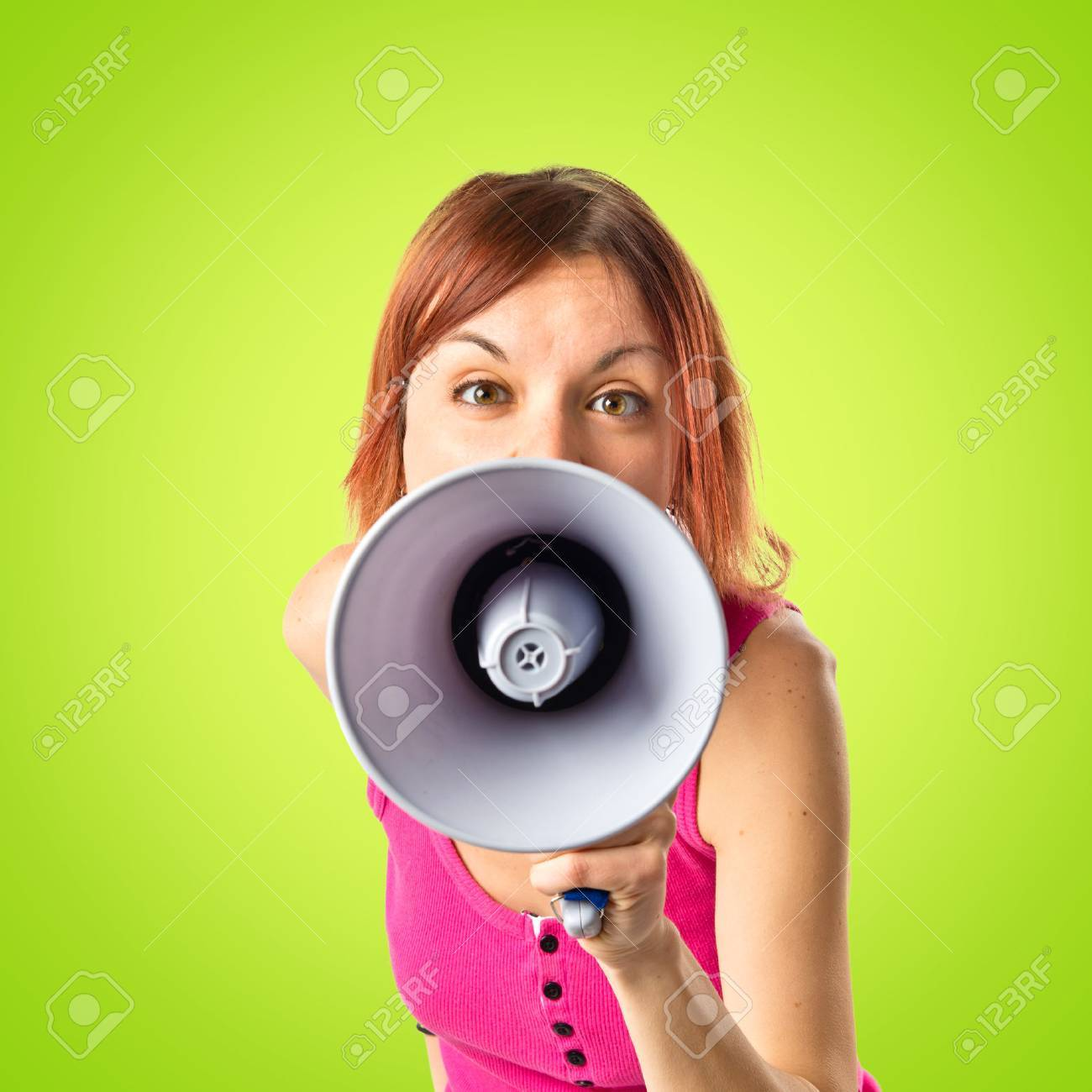 Redhead girl shouting with a megaphone over green background Stock Photo - 33321471