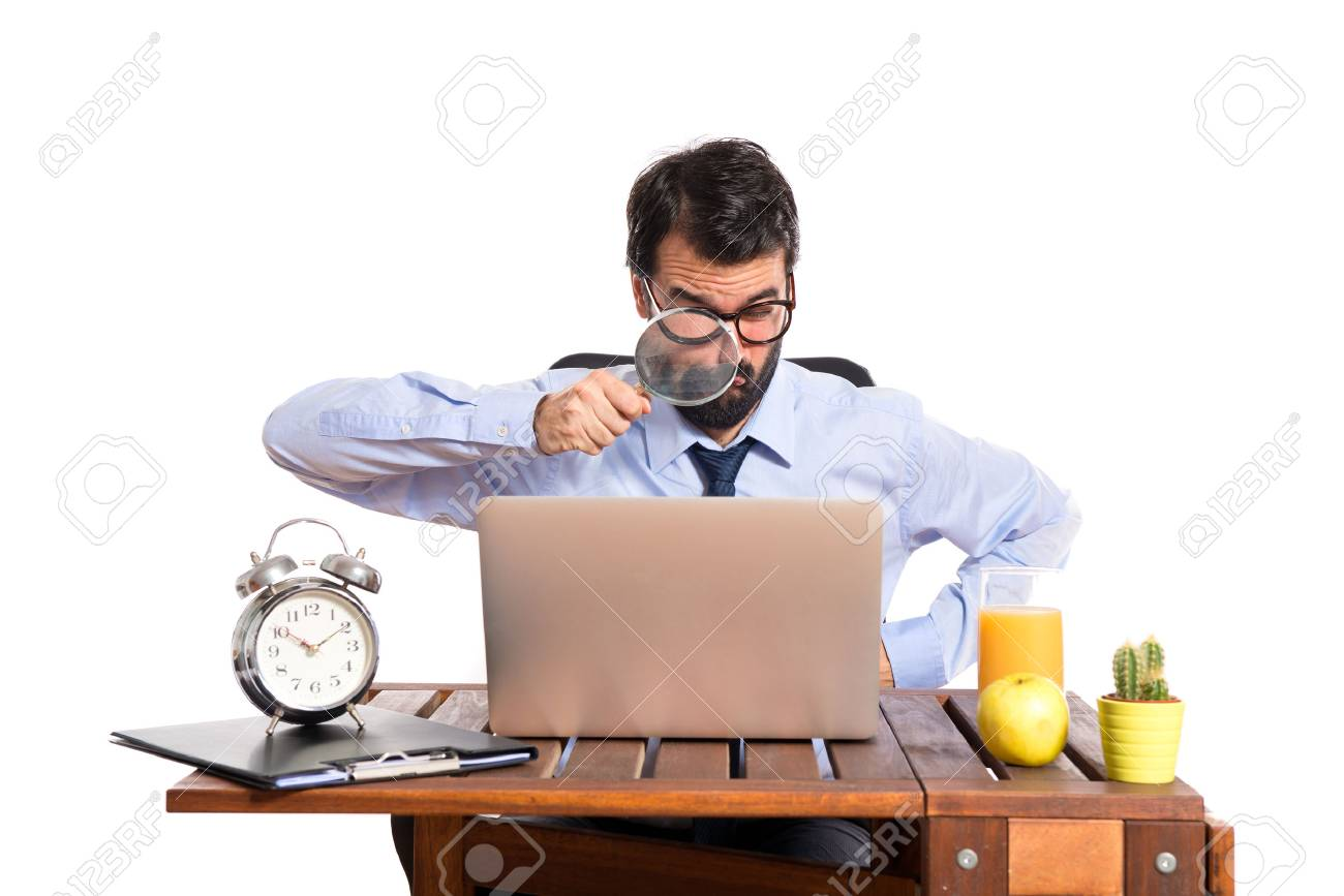 Businessman in his office with magnifying glass - 33527413