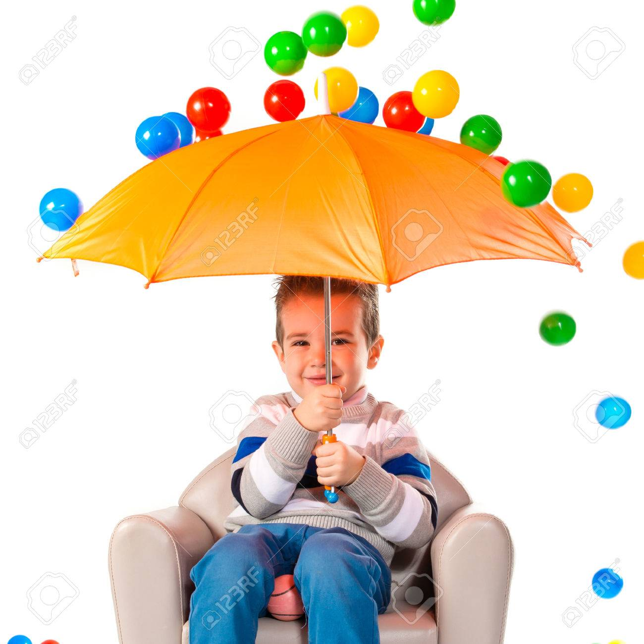 kid holding an umbrella around colorful balls stock photo picture