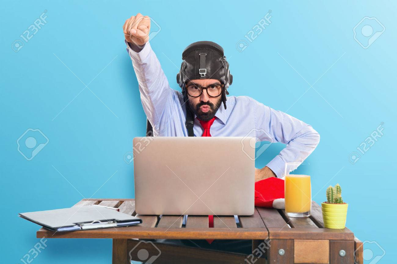 Businessman in his office with pilot hat - 40989416