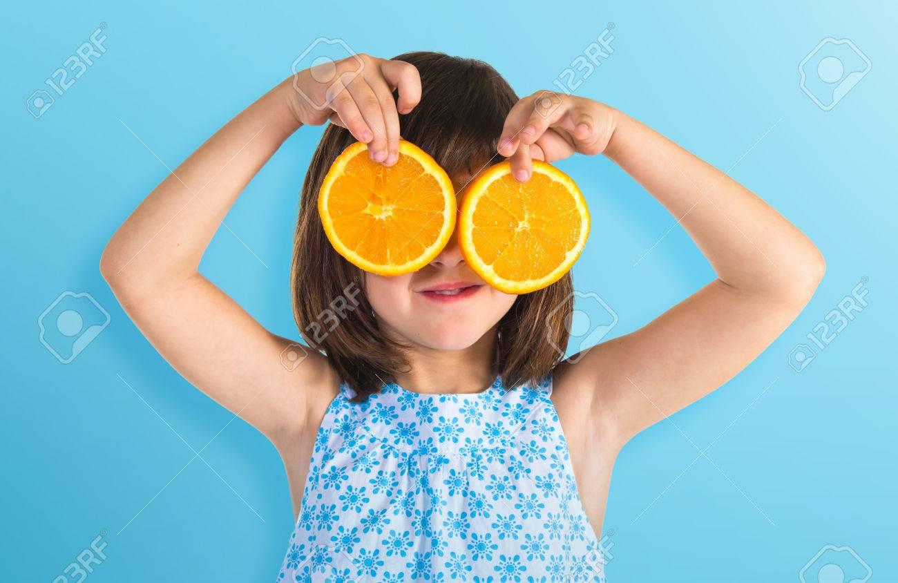 Girl holding orange slices as glasses - 41809390