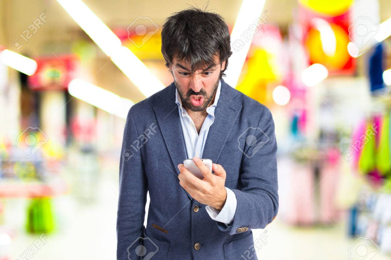Angry man talking to mobile over white background - 43936576