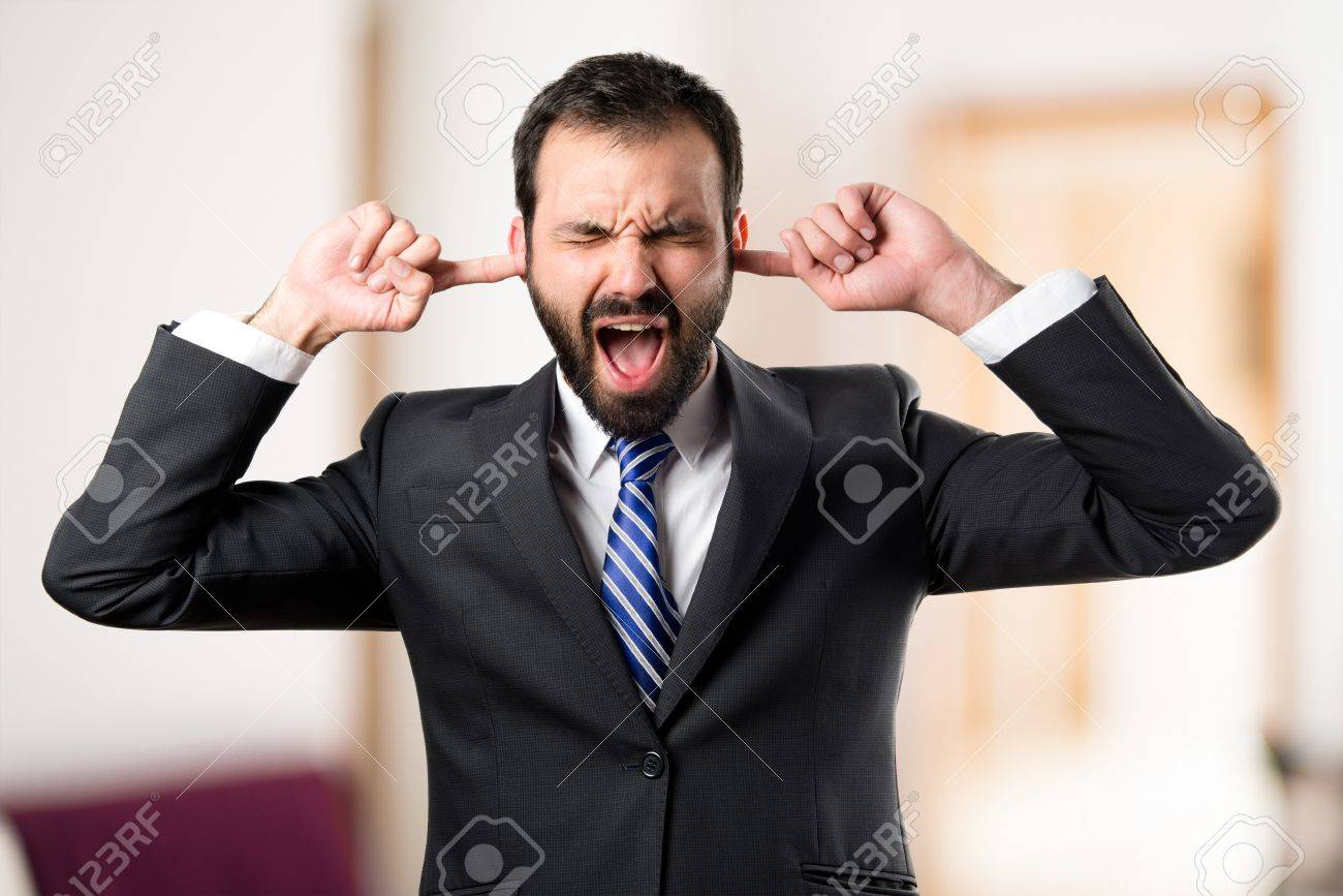 business man covering her ears over white background - 73719065