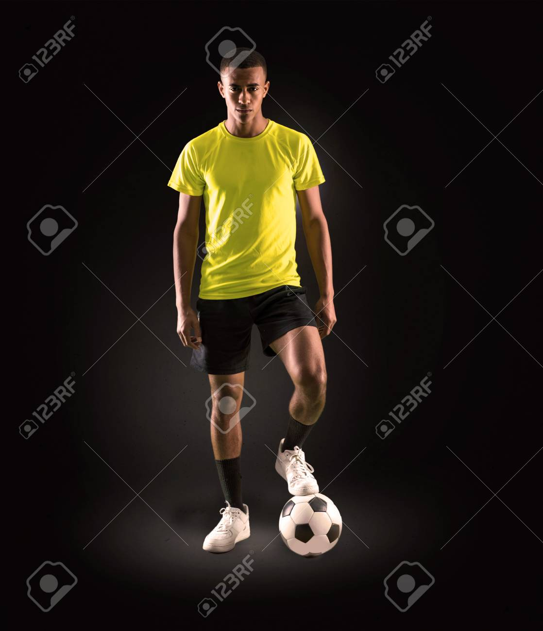 Soccer player man with dark skinned playing on dark background - 113780774