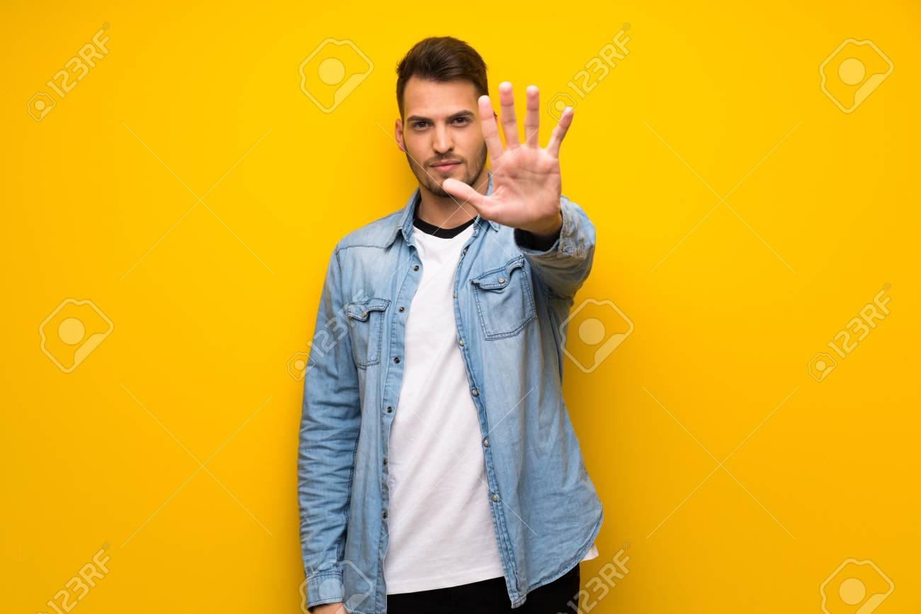 Handsome man over yellow wall making stop gesture denying a situation that thinks wrong - 119131978