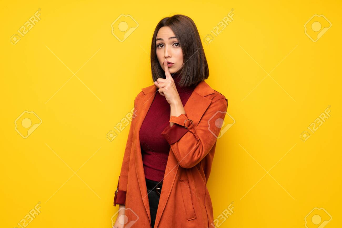 Young woman with coat showing a sign of silence gesture putting finger in mouth - 119423101