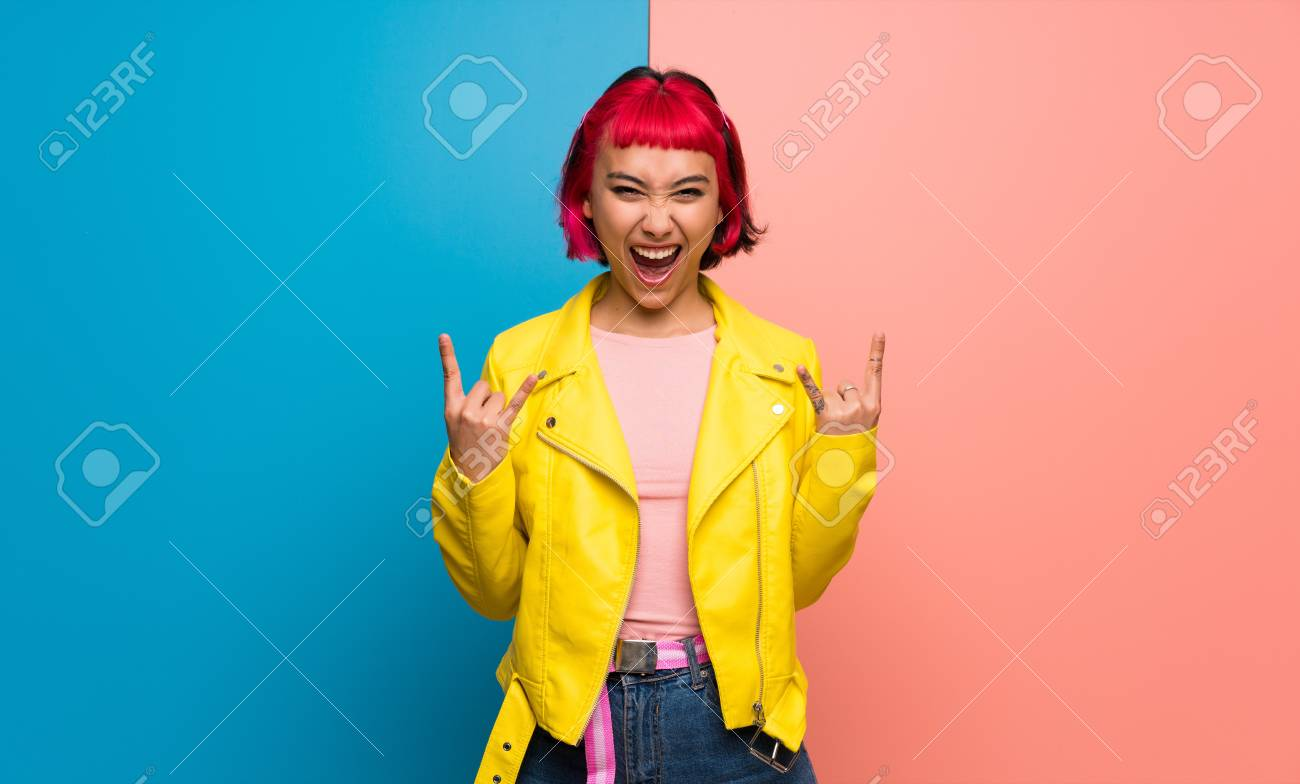 Young woman with yellow jacket making rock gesture - 120838130