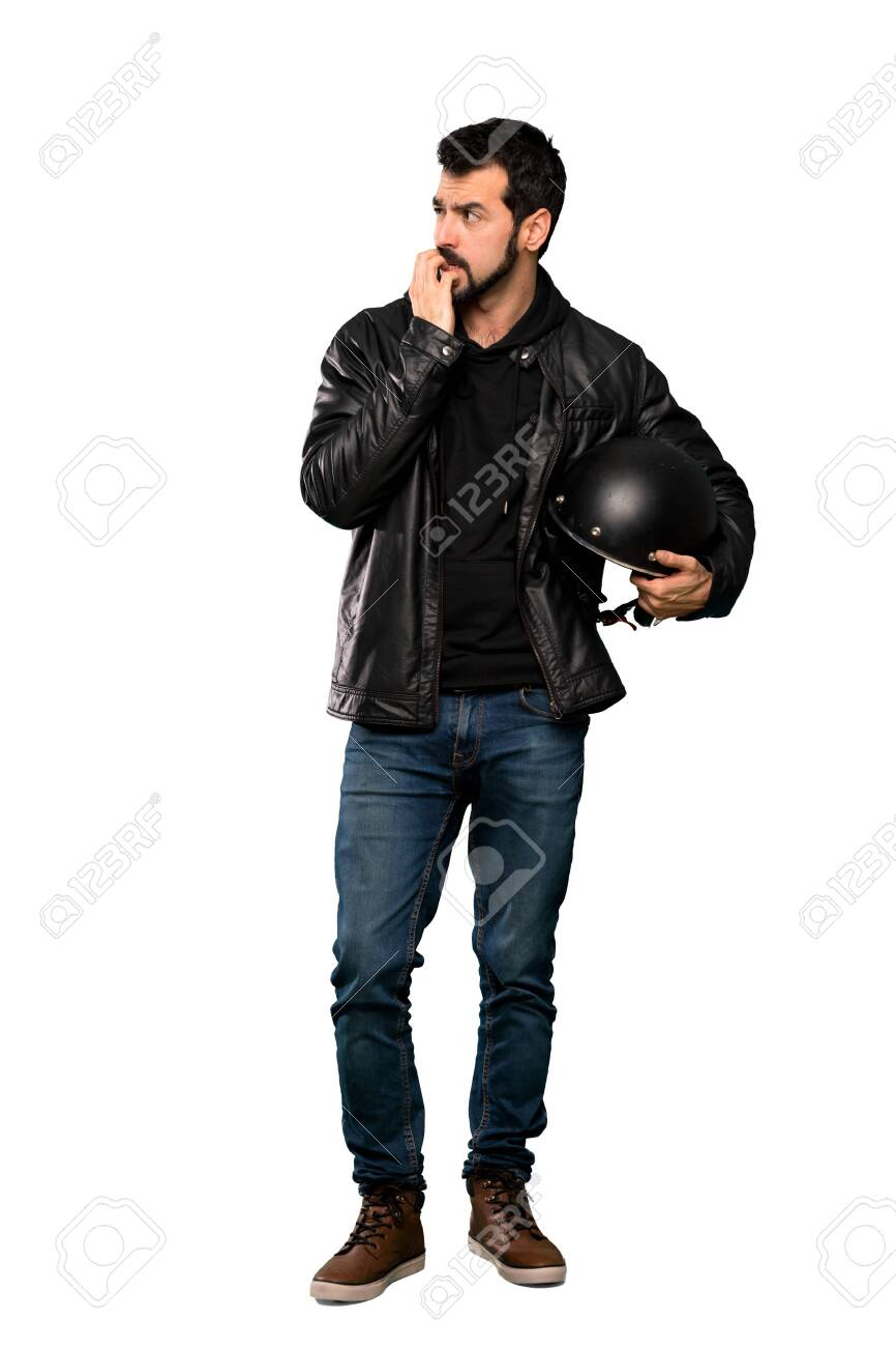 Full-length shot of Biker man nervous and scared putting hands to mouth over isolated white background - 121048806