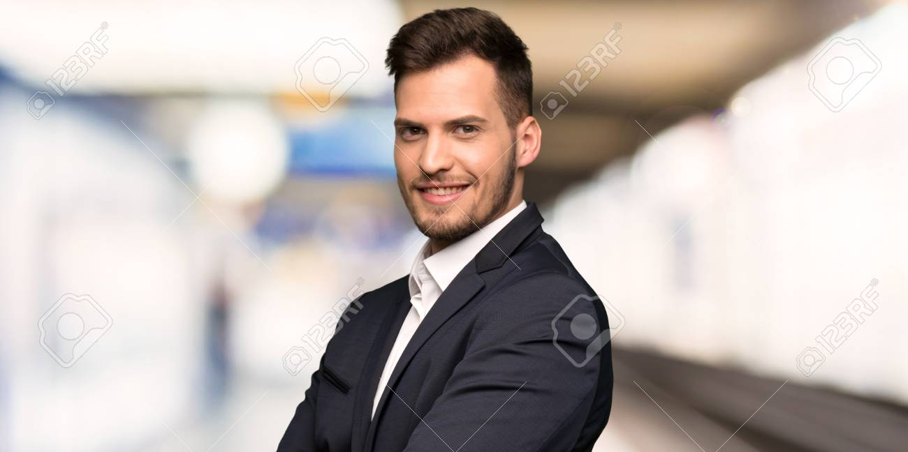 Handsome business man with arms crossed and looking forward at indoors - 123588576