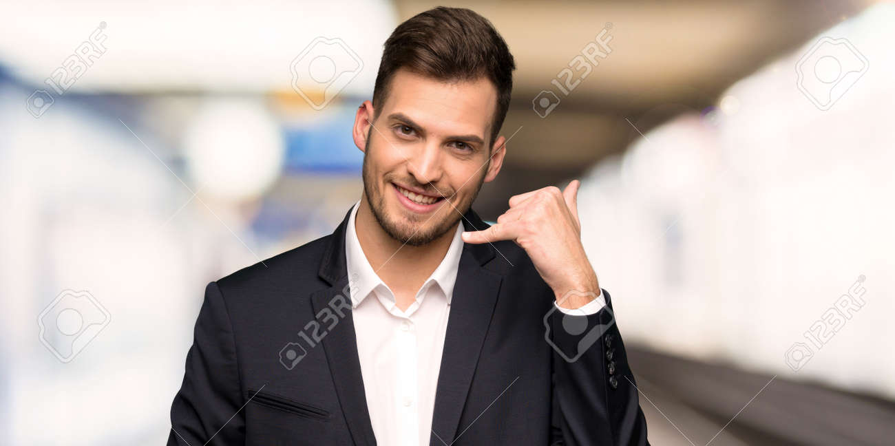 Handsome business man making phone gesture. Call me back sign at indoors - 123666791