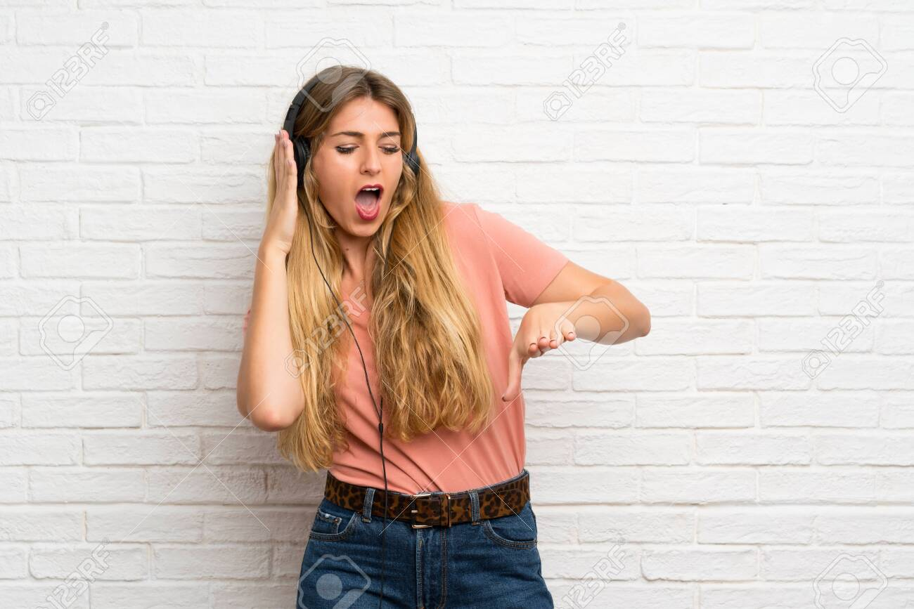 Young blonde woman over white brick wall listening to music with headphones - 127037500