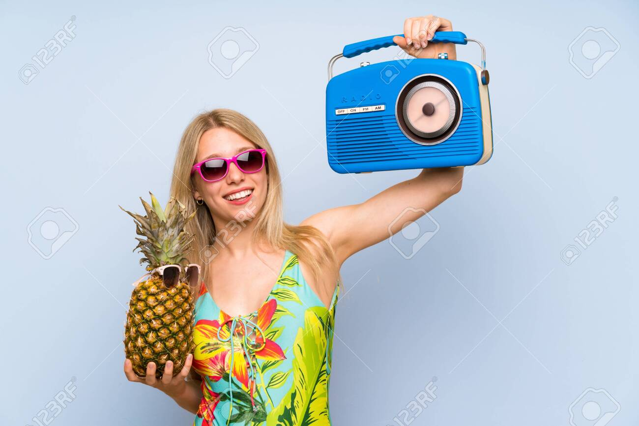 Young woman in swimsuit holding a pineapple with sunglasses and a radio - 126980492