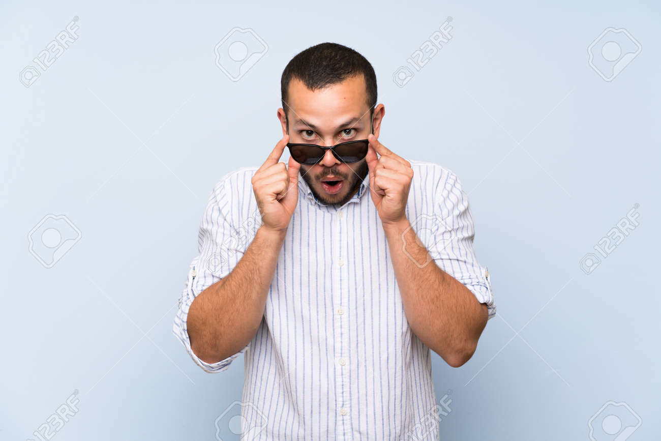 Colombian man over isolated blue wall with glasses and surprised - 128148172