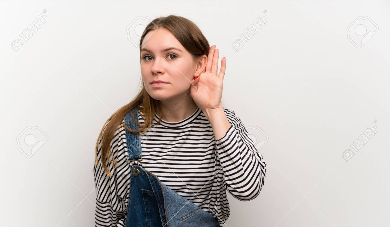 Young woman in dungarees over white wall listening something - 128617746