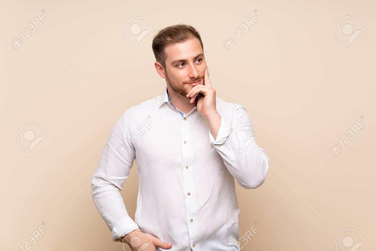 Blonde man over isolated background thinking an idea while looking up - 129665836
