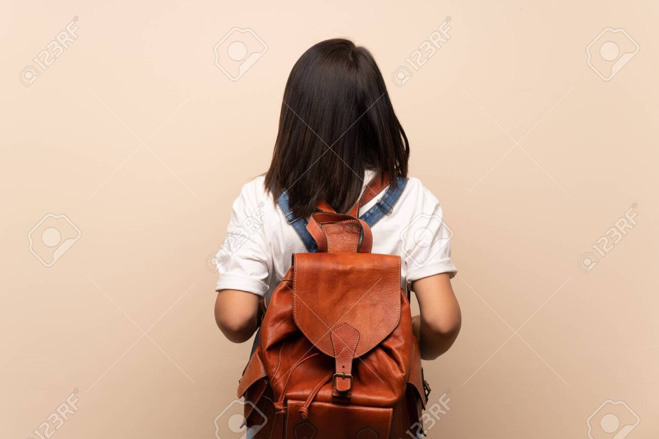 Young Mexican woman over isolated background with backpack - 130156292