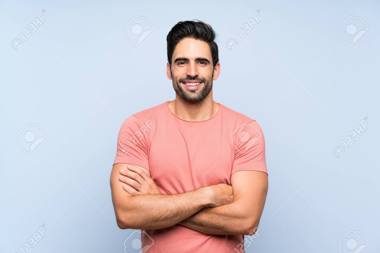 Handsome young man in pink shirt over isolated blue background keeping the arms crossed in frontal position - 130592146