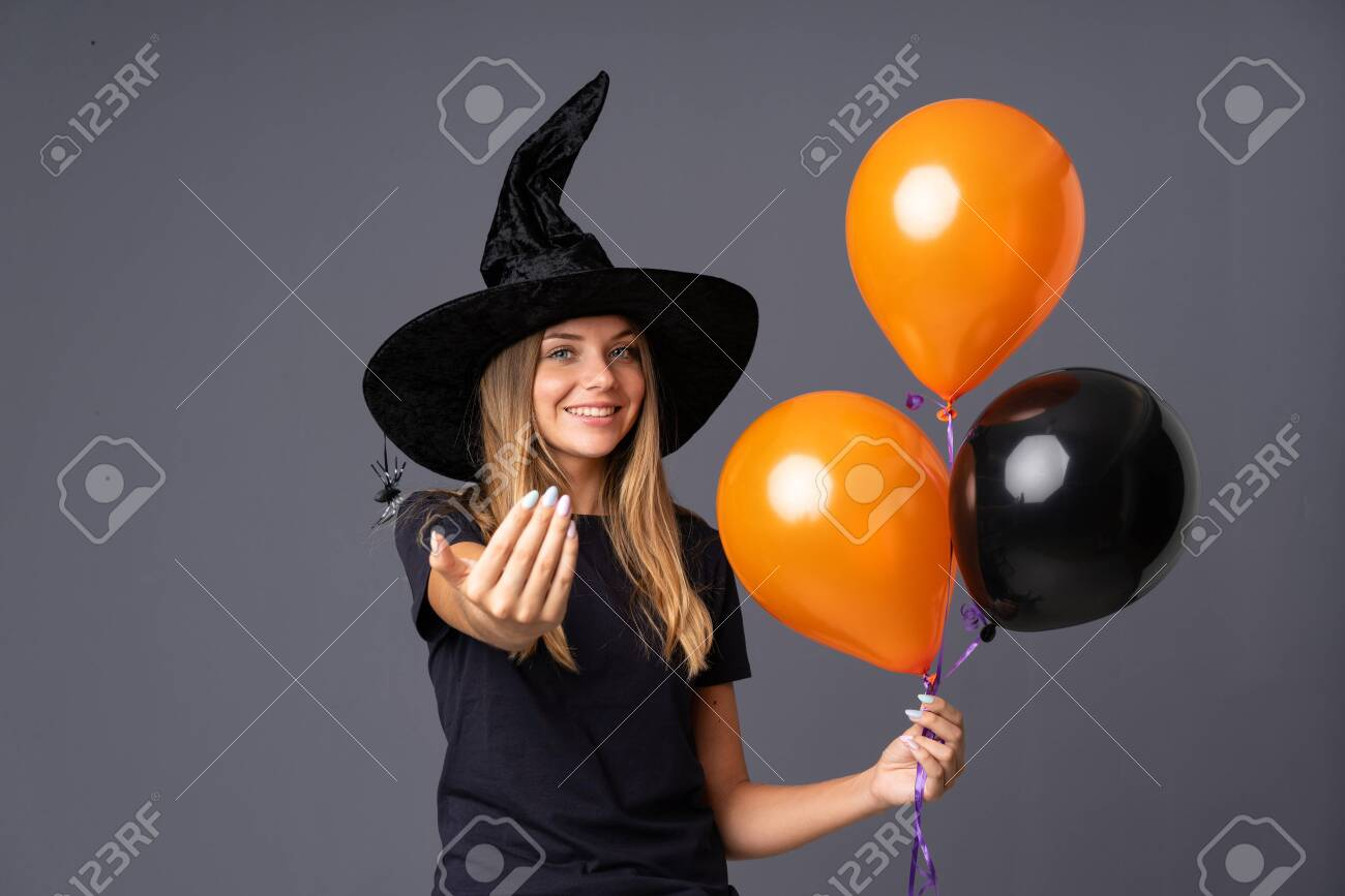 Young witch holding black and orange air balloons inviting to come - 131597503