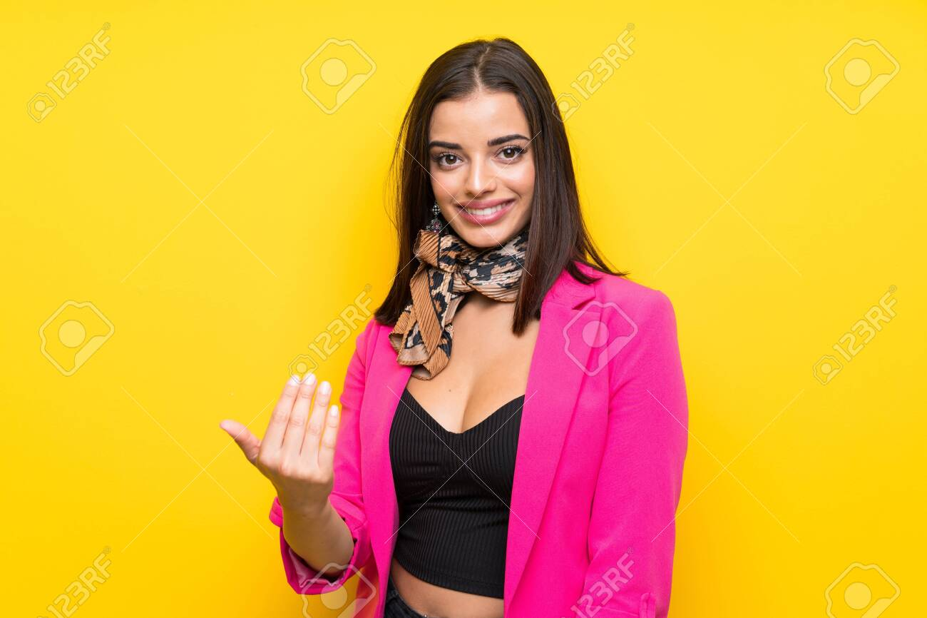 Young woman over isolated yellow background inviting to come - 131833200