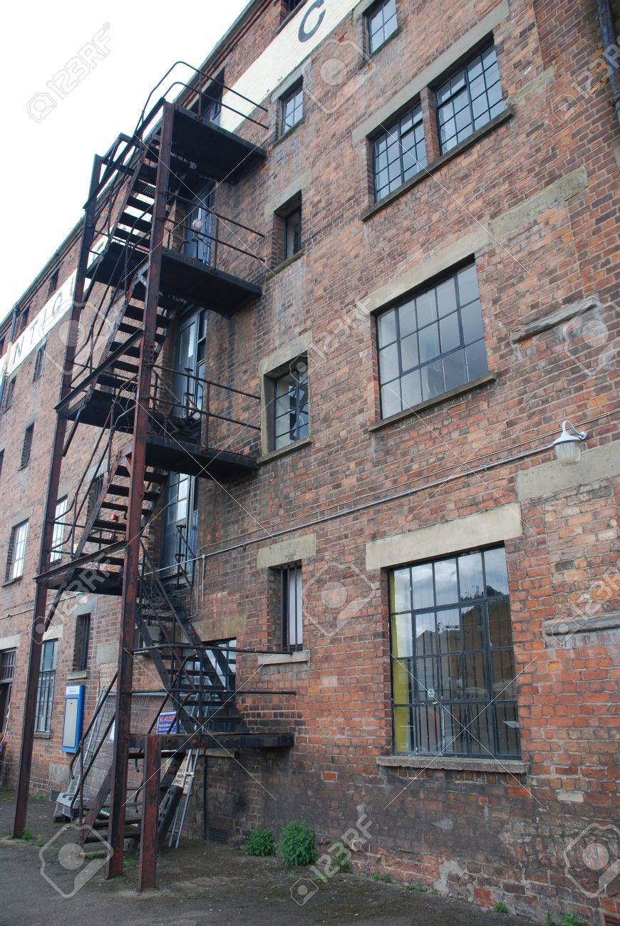 rusty fire escape stairs in a old brick wall building Stock Photo - 7210714