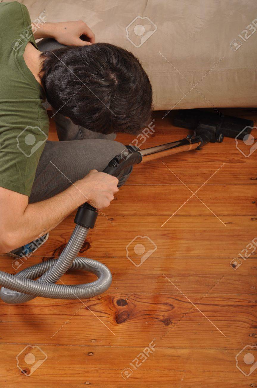 back view of a young man with vacuum cleaner doing the housework Stock Photo - 7377724