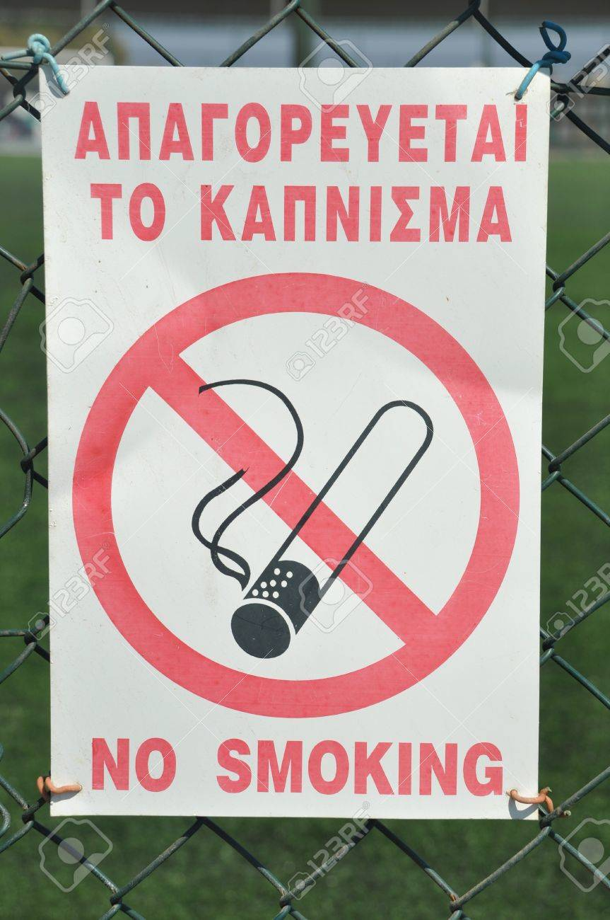 forbidden to smoke sign hanging on a sports court fence (greek and english language) Stock Photo - 7884144