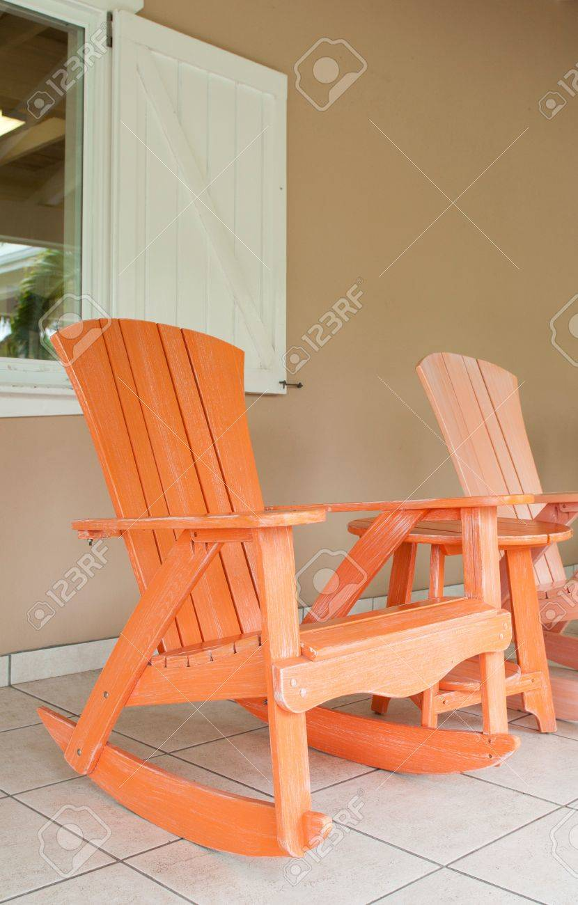 Orange And Pink Wooden Rocking Chairs On A Porch (usual Setting On A  Tropical Resort