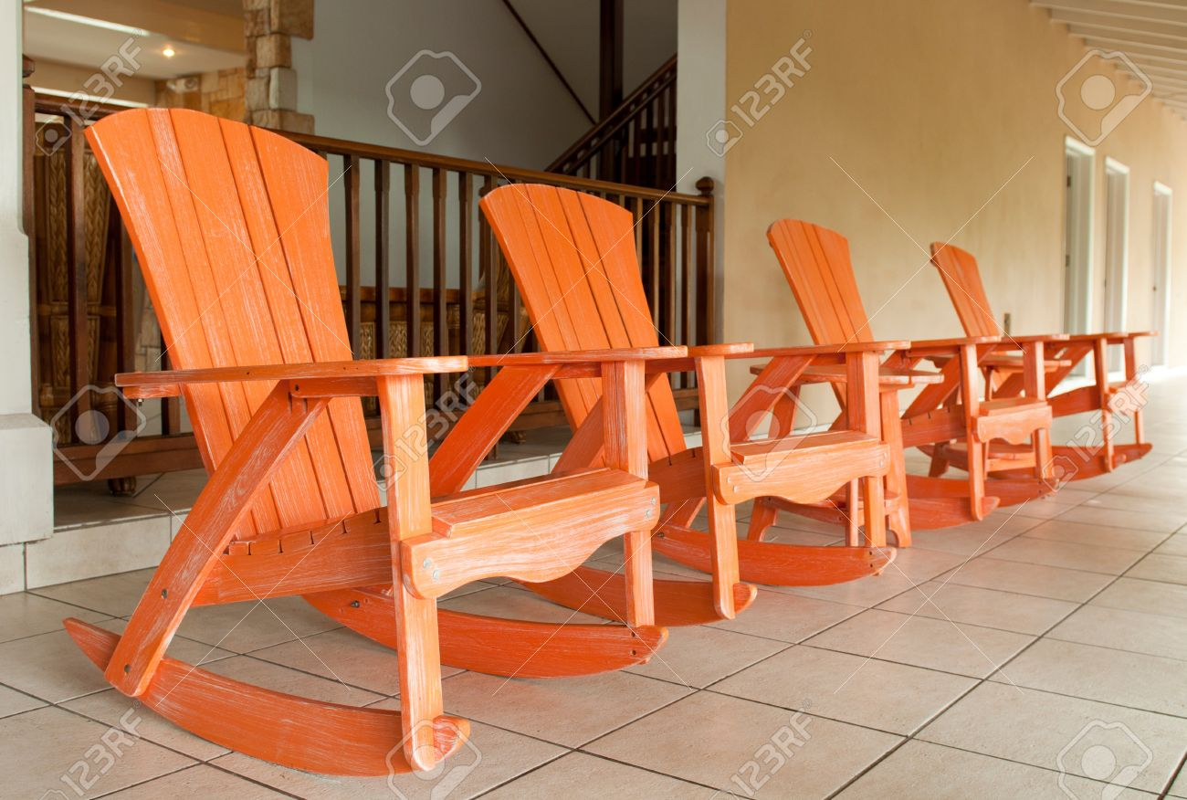 row of orange wooden rocking chairs on a porch (usual setting