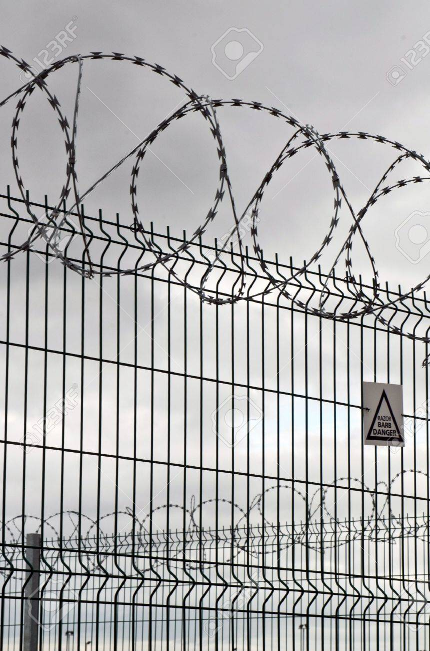 Circular Barbed Wire And Fence On A Very Overcast Day Stock Photo ...