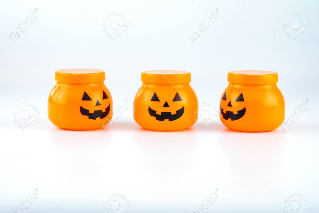 Tres juguetes de plástico jack o linterna de calabaza para la decoración de halloween aislado sobre fondo blanco