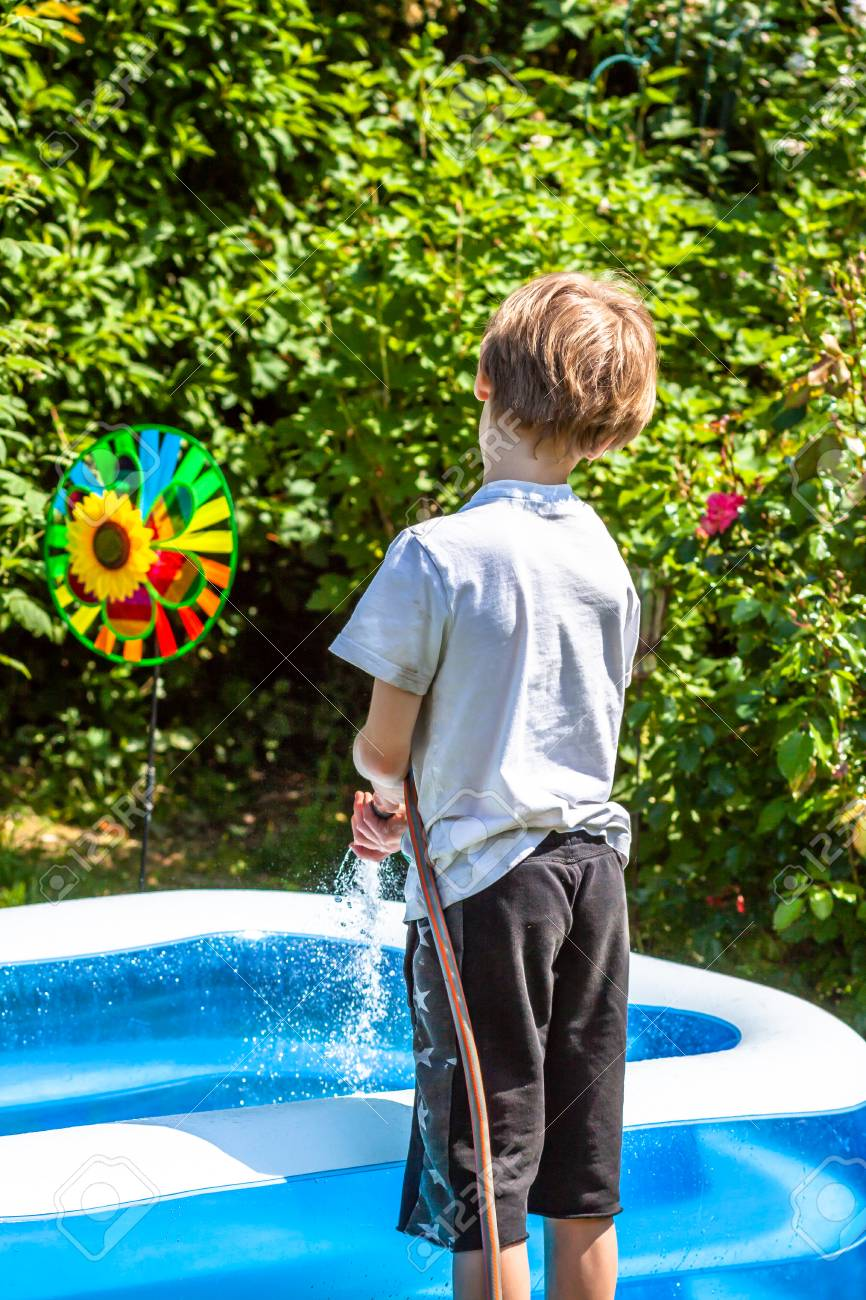 Little boy filling filling swimming pool with water