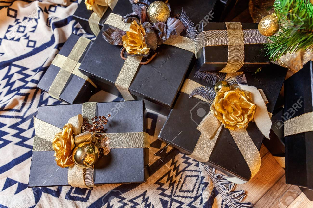 Black Paper Gift Boxes With Golden Ribbon Bow Near The Christmas