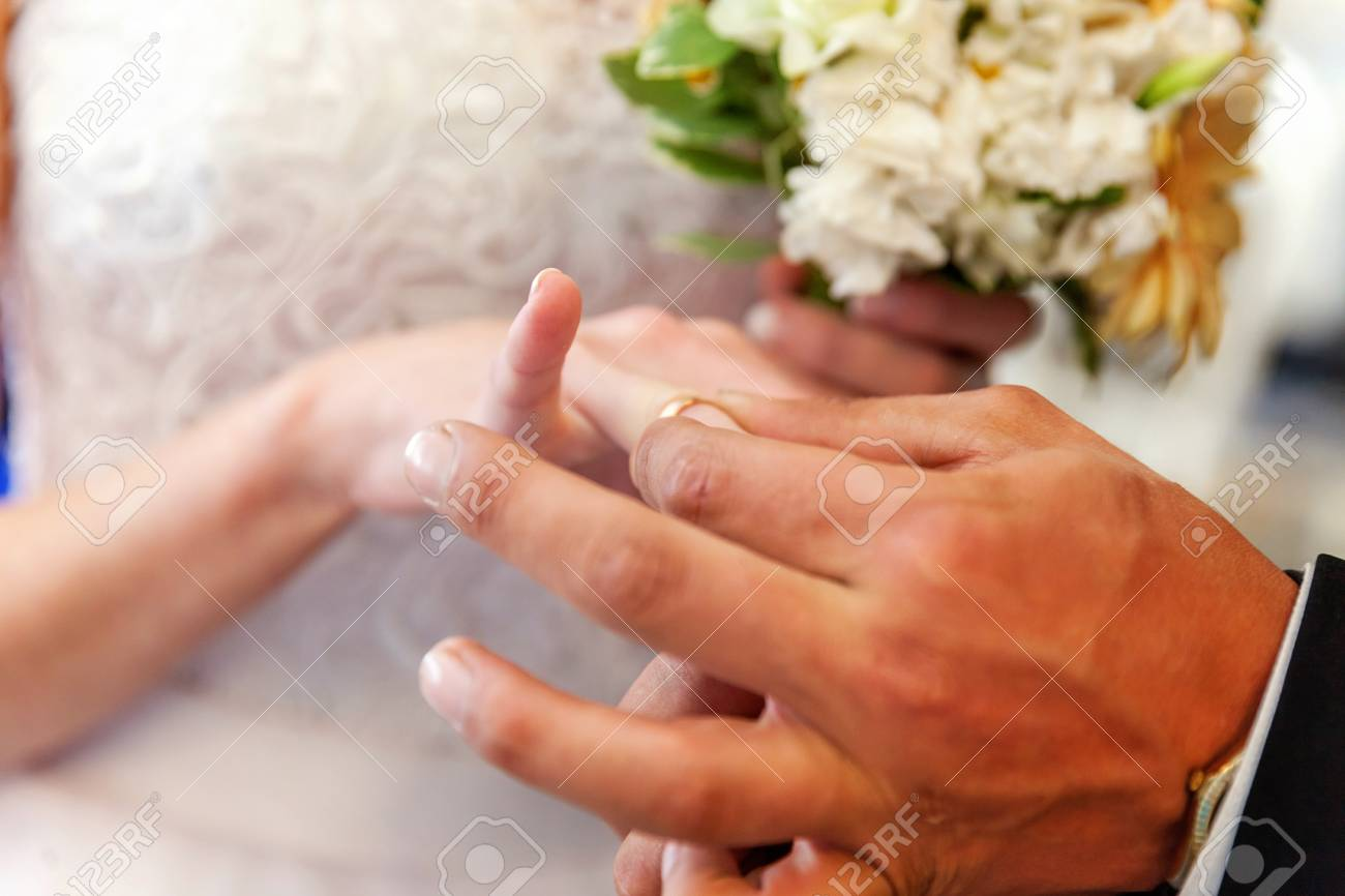 Marriage hands with rings grooms hand putting a wedding ring marriage hands with rings grooms hand putting a wedding ring on the brides finger stock junglespirit Images