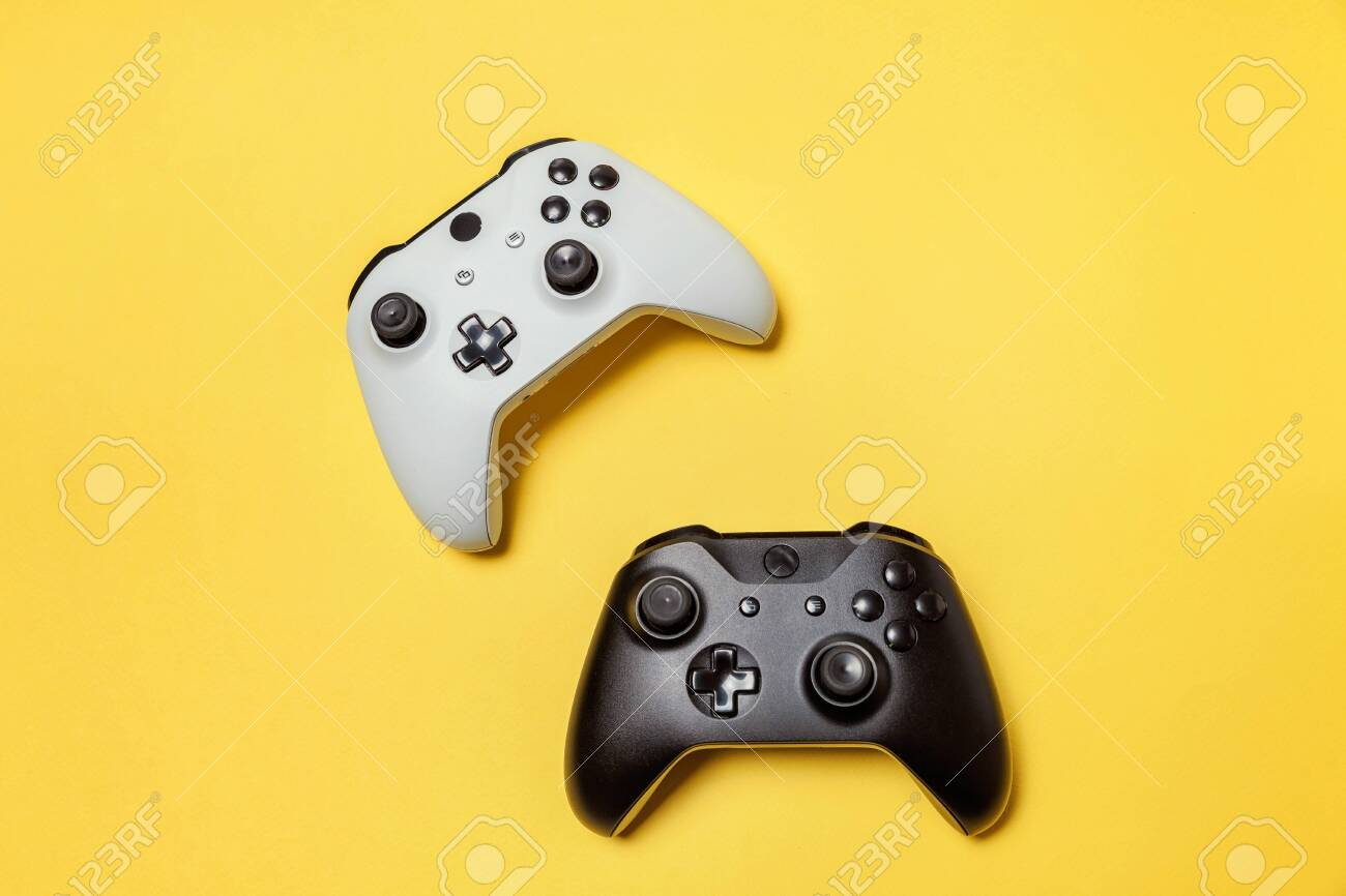 White and black two joystick gamepad, game console on yellow colourful trendy modern fashion pin-up background. Computer gaming competition videogame control confrontation concept. Cyberspace symbol - 120872715