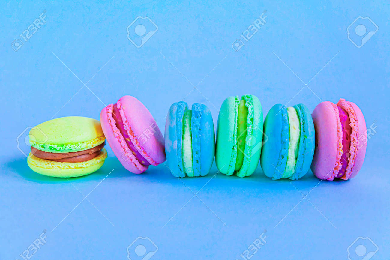 Sweet almond colorful pink blue yellow green macaron or macaroon dessert cake isolated on trendy blue pastel background. French sweet cookie. Minimal food bakery concept. Flat lay top view copy space - 159123076