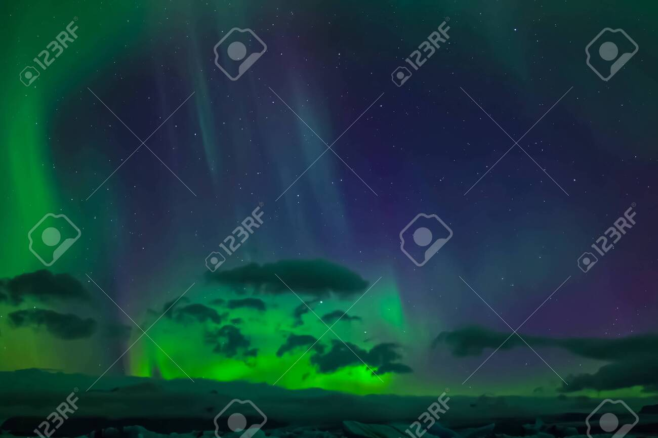 Aurora borealis in the night northern sky. Ionization of air particles in the upper atmosphere. - 135666863