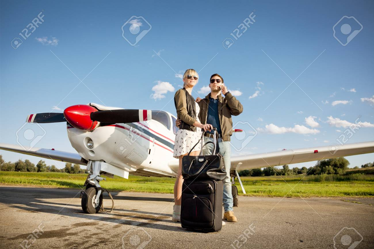 young couple standing by propeller airplane man using phone stock