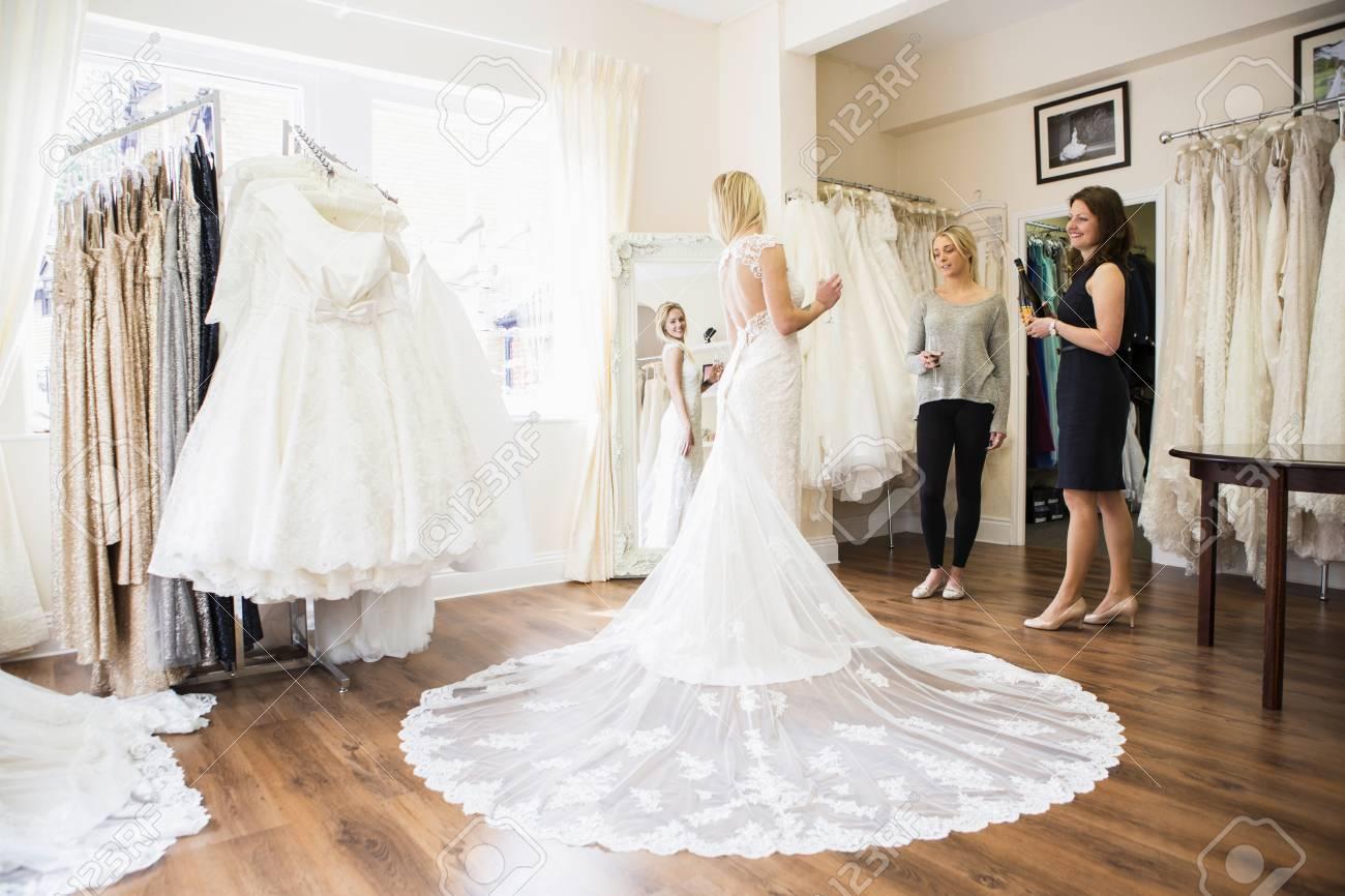 Female Customer In Bridal Shop Trying On Wedding Dress Stock Photo ...