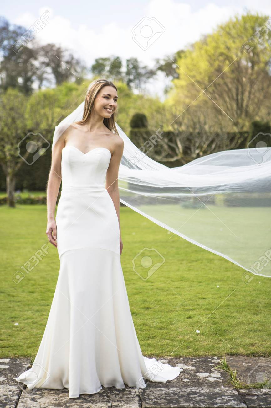 Bride Showing Off Wedding Dress Outdoors Stock Photo, Picture And ...