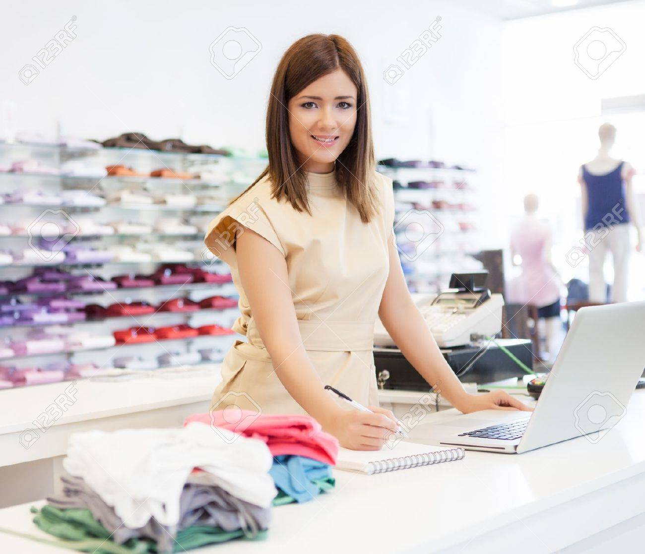 a shop assistant standing at the checkout desk stock photo a shop assistant standing at the checkout desk stock photo 19563812