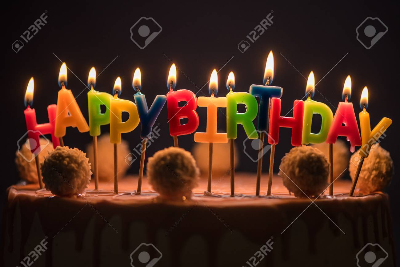Lit Happy Birthday Candles On Top Of Pink Cake Stock Photo