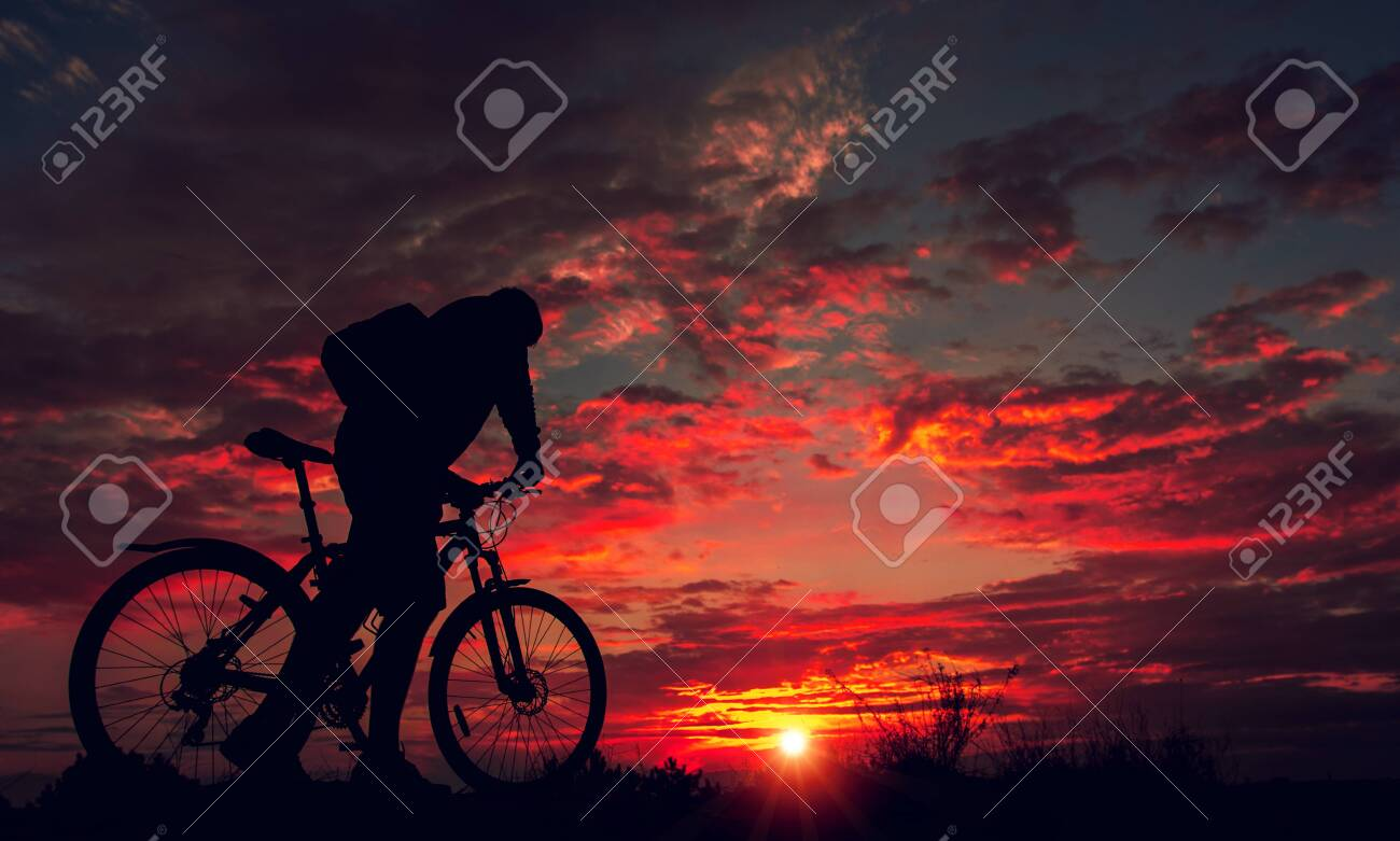 cyclist on the mountain with a bicycle, admiring the fiery sunset. - 135231326